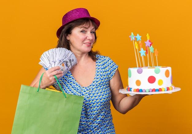 Szczęśliwa kobieta w średnim wieku w imprezowym kapeluszu trzymająca papierową torbę z prezentami trzymająca tort urodzinowy i gotówkę uśmiechnięta szeroko świętująca przyjęcie urodzinowe stojąca nad pomarańczową ścianą