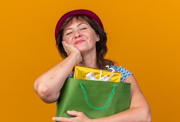 Szczęśliwa kobieta w średnim wieku w imprezowym kapeluszu trzymająca papierową torbę z prezentami urodzinowymi z zamkniętymi oczami uśmiecha się radośnie świętując urodziny stojąc nad pomarańczową ścianą
