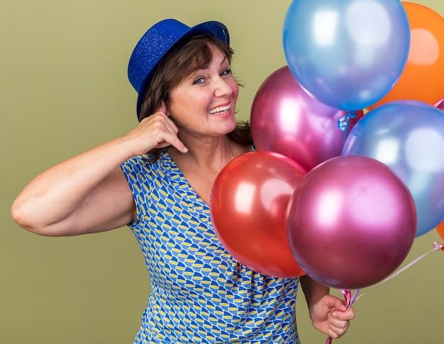 """Szczęśliwa kobieta w średnim wieku w imprezowym kapeluszu z wiązką kolorowych balonów uśmiecha się radośnie, wykonując gest """"zadzwoń do mnie"""