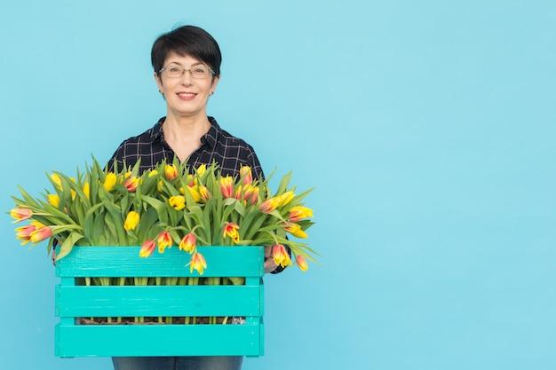 Szczęśliwa kobieta w średnim wieku w okularach, trzymając pudełko tulipanów na niebieskim tle z miejsca na kopię