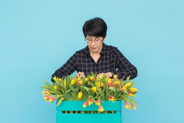 Szczęśliwa kobieta w średnim wieku w okularach, trzymając pudełko tulipanów na niebieskim tle