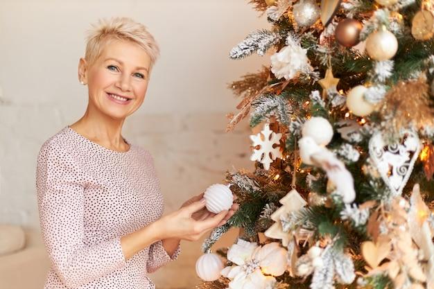 Szczęśliwa kobieta w średnim wieku z blond krótką fryzurą trzymająca białą bombkę z radosnym uśmiechem podczas dekorowania choinki w salonie, przygotowując się do ferii zimowych