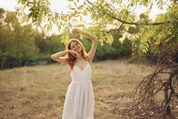 Szczęśliwa kobieta w sukience na charakter, w pobliżu zielonych liści drzew i krzewów w tle