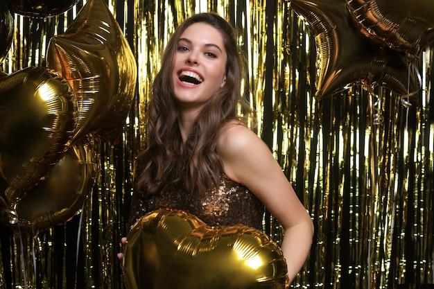 Szczęśliwa kobieta w świątecznym stroju trzyma złote balony.