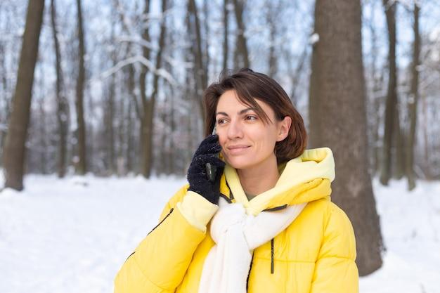 Szczęśliwa kobieta w świetnym nastroju spaceruje po zaśnieżonym zimowym lesie i wesoło rozmawia przez telefon, ciesząc się czasem na świeżym powietrzu w parku