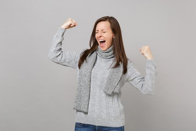 Szczęśliwa kobieta w szary sweter szalik z zamkniętymi oczami krzyczeć, pokazując biceps, mięśnie na białym tle na szarym tle. zdrowy styl życia moda, emocje ludzi, koncepcja zimnej pory roku. makieta miejsca na kopię.