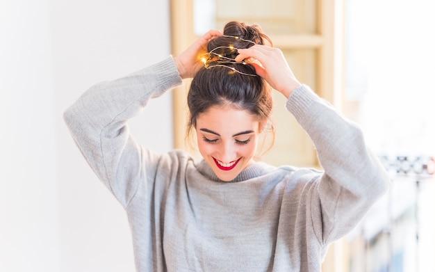 Szczęśliwa kobieta w szarych mienie rękach na włosy z girlandą