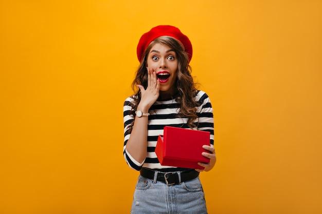 Szczęśliwa kobieta w szoku w czerwonym berecie trzyma pudełko. raduje się zdziwiona dama z falującymi włosami w jasnym kapeluszu i koszuli w paski.