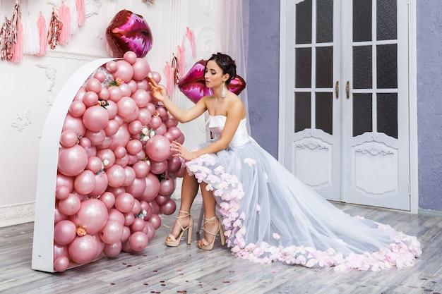 Szczęśliwa kobieta w tiulowej sukni z różowymi balonami. luksus