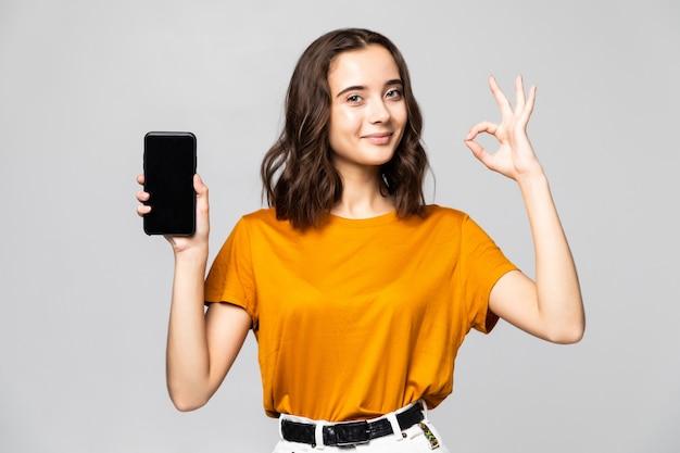 Szczęśliwa kobieta w ubranie pokazuje pusty ekran smartfona z w porządku gestem na szarej ścianie
