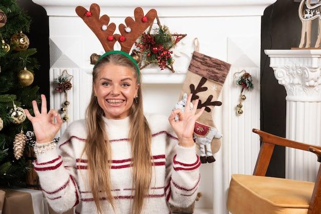 Szczęśliwa kobieta w uszach jelenia, dając znak ok przy kominku.