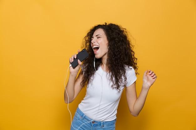 Szczęśliwa kobieta w wieku 20 lat z kręconymi włosami śpiewa, trzymając smartfon jak mikrofon i słuchając muzyki przez słuchawki izolowane na żółto