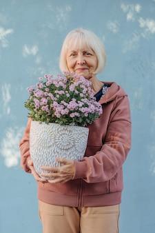 Szczęśliwa kobieta w wieku niosąc garnek z kwiatami. wesoła starsza kobieta w stylowej odzieży wierzchniej uśmiechnięta