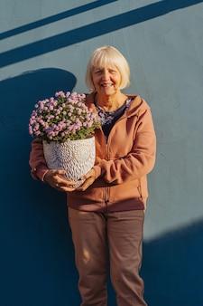 Szczęśliwa kobieta w wieku niosąca garnek z kwiatami. wesoła starsza kobieta uśmiechnięta