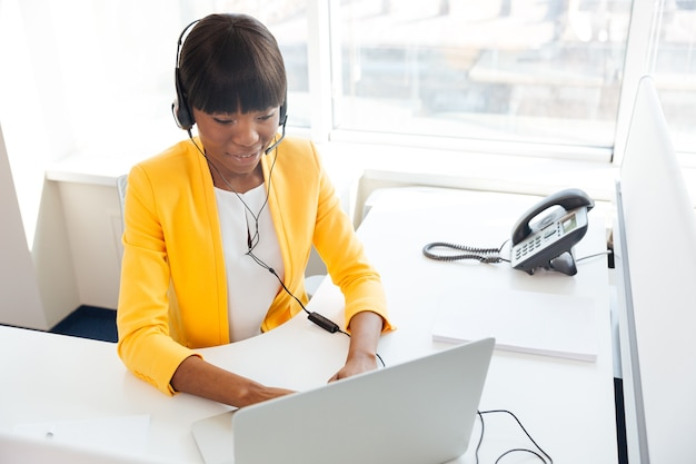 Szczęśliwa kobieta w zestawie słuchawkowym za pomocą laptopa w biurze