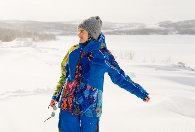 Szczęśliwa kobieta w zimowym garniturze na tle zaśnieżonego pola