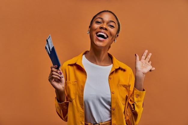 Szczęśliwa kobieta w żółtej koszuli uśmiecha się do kamery z paszportem z biletami w ręku. koncepcja podróży