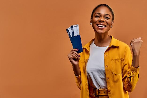 Szczęśliwa kobieta w żółtej koszuli uśmiecha się z paszportem z biletami i pokazuje gest zwycięstwa. koncepcja podróży