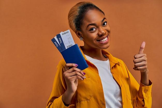 Szczęśliwa kobieta w żółtej koszuli uśmiecha się z paszportem z biletami i pokazuje jak gest. koncepcja podróży