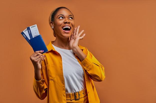 Szczęśliwa kobieta w żółtej koszuli uśmiecha się z paszportem z biletami w ręku. koncepcja podróży