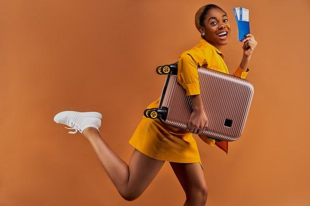 Szczęśliwa kobieta w żółtym garniturze w kolczykach ucieka z walizką z paszportem i biletami w ręku. koncepcja podróży