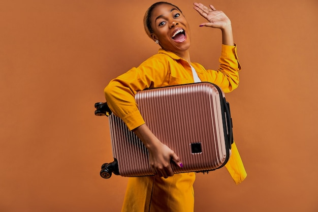 Szczęśliwa kobieta w żółtym garniturze w kolczykach z walizką macha ręką do kamery. koncepcja podróży