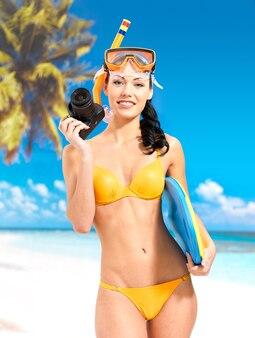 Szczęśliwa kobieta w żółtym stroju kąpielowym z aparatem cyfrowym robienia zdjęć na plaży