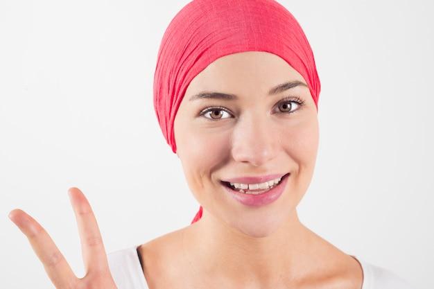 Szczęśliwa kobieta walczy z rakiem z różowym szalikiem