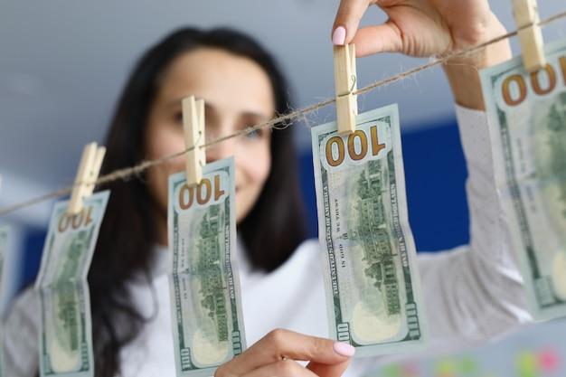 Szczęśliwa kobieta wisi czyste dolary na spinaczach do bielizny, aby wysuszyć brudną koncepcję prania brudnych pieniędzy