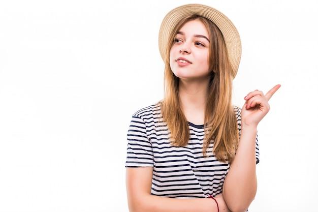 Szczęśliwa kobieta wskazuje strona nad białą ścianą