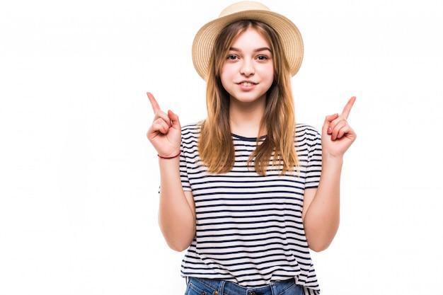 Szczęśliwa kobieta wskazuje up nad białą ścianą