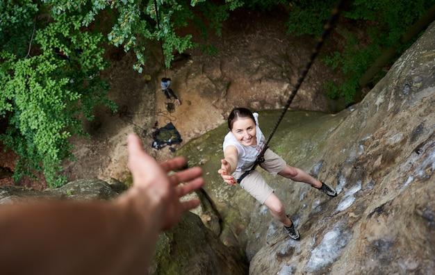 Szczęśliwa kobieta wspinaczka skały. beztroski turysta uśmiecha się do swojego przyjaciela. mężczyzna pomaga jego przyjacielowi wspinać się skałę.