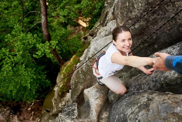 Szczęśliwa kobieta wspinaczki skał trekking na świeżym powietrzu. beztroski turysta uśmiecha się do swojego przyjaciela. mężczyzna pomaga wspinać się skałę