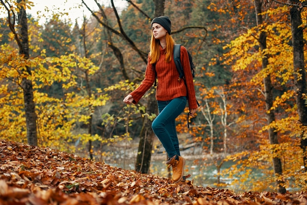 Szczęśliwa kobieta wycieczkowicz z plecakiem na plecach w dżinsach i czerwonym swetrze w jesiennym parku leśnym