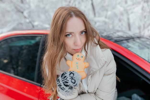Szczęśliwa kobieta wygląda przez okno samochodu, trzyma w rękach ciasteczko w postaci mężczyzny. zimowy las.