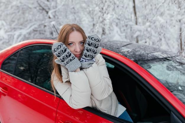 Szczęśliwa kobieta wygląda przez okno samochodu, zasłaniając twarz rękami. zimowy las.
