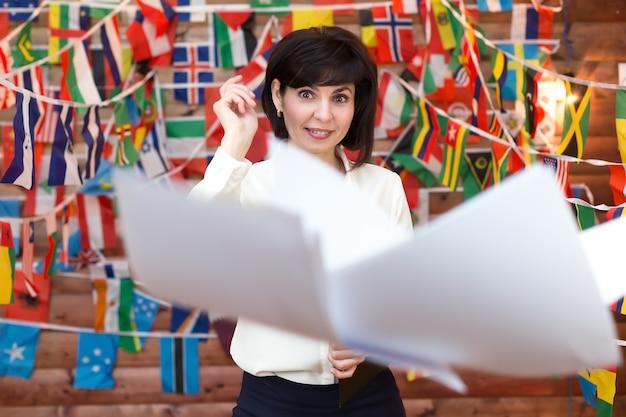 Szczęśliwa kobieta wyrzuca papierkową robotę w powietrze.