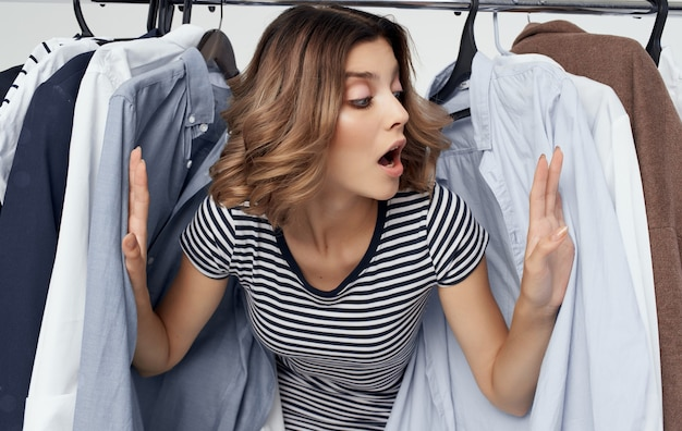 Szczęśliwa kobieta wystającym zza ubrania w garderobie zakupy młodzieży