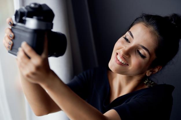 Szczęśliwa kobieta z aparatu fotograficznego w pomieszczeniu z oknem w tle