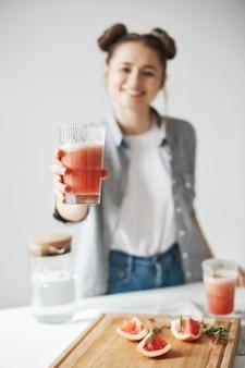 Szczęśliwa kobieta z babeczkami uśmiecha się rozciągający detox grapefruitowego smoothie nad biel ścianą. zdrowa dieta. skoncentruj się na szkle.
