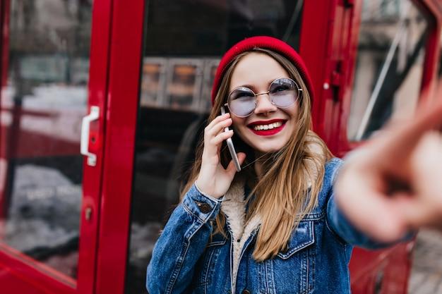 Szczęśliwa kobieta z białą skórą rozmawia przez telefon.