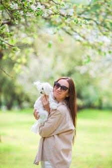 Szczęśliwa kobieta z białym psem w przyrodzie. dziewczyna bawi się ze szczeniakiem w parku