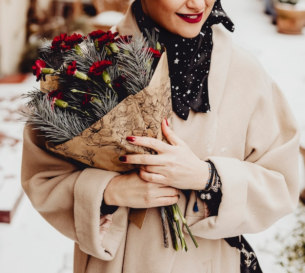 Szczęśliwa kobieta z bukietem kwiatów w okresie zimowym