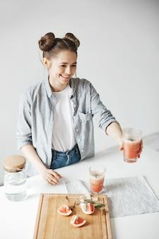Szczęśliwa kobieta z bułkami uśmiecha się rozciąganie szkła z grejpfrutowym detox smoothie dla kogoś. tło białe ściany. zdrowa dieta.