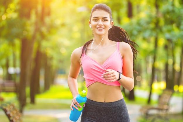 Szczęśliwa kobieta z butelką biegającą w parku na słonecznym tle