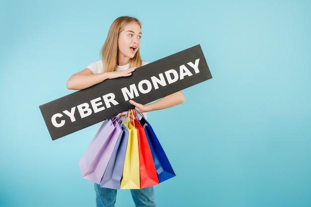 Szczęśliwa kobieta z cyber poniedziałku znakiem i kolorowymi torba na zakupy odizolowywającymi nad błękitem