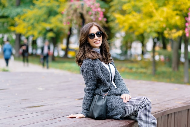 Szczęśliwa kobieta z czarującym uśmiechem i ciemnymi włosami relaksuje się w jesiennym parku w słońcu. siedzi na drewnianym stole i śmieje się w parku pośród żółtych drzew i krzewów.