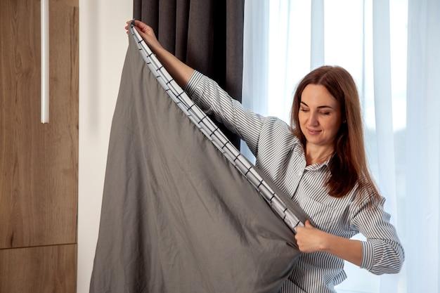 Szczęśliwa kobieta z długimi rudymi włosami jest składana pościel ustawiona na łóżku w pokoju z miejscem na kopię. produkcja tekstyliów organicznych. pościel ozdobiona jest paskami w formie klatki. różne poduszki