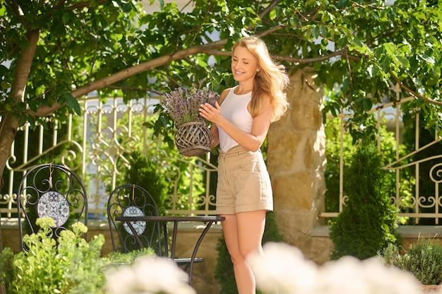 Szczęśliwa kobieta z doniczką kwiatów w ogrodzie