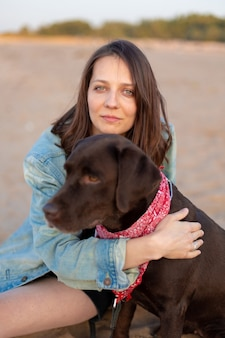 Szczęśliwa kobieta z europejskiego kraju o ciemnych włosach w dżinsowej kurtce w stylu vintage, przytulająca psa i uśmiechnięta